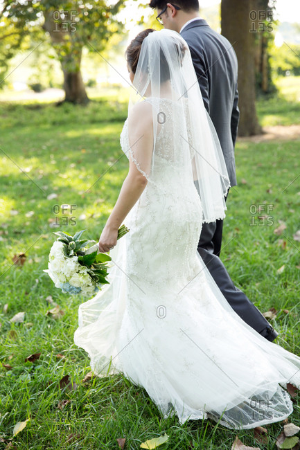 Bride and groom walking across a green lawn