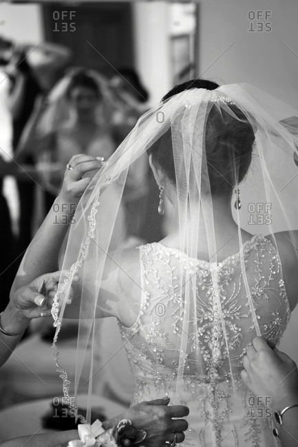 Bride adjusting her veil in a mirror before her wedding