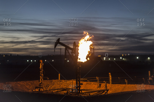 Gas flare with pump jacks in the backgrounds