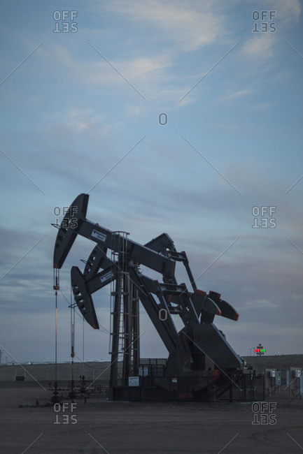 4/29/2015, Williston, North Dakota: Three pump jacks at an oil well site