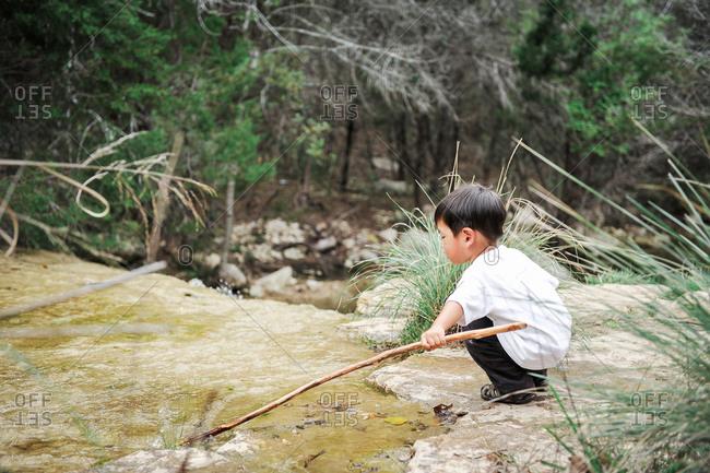Boy poking stick into  stream