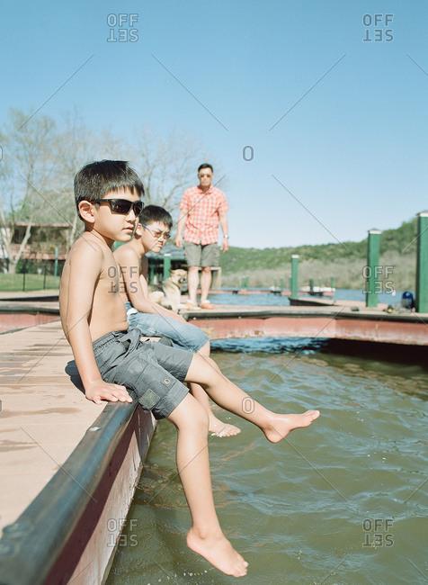 Kids relaxing on lake dock
