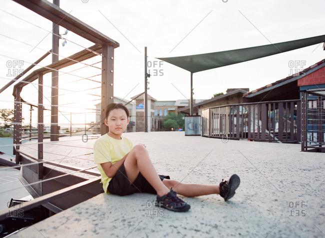 Boy sitting on elevated walkway