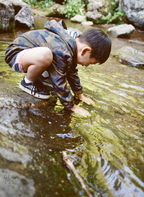 Boy putting hands in stream