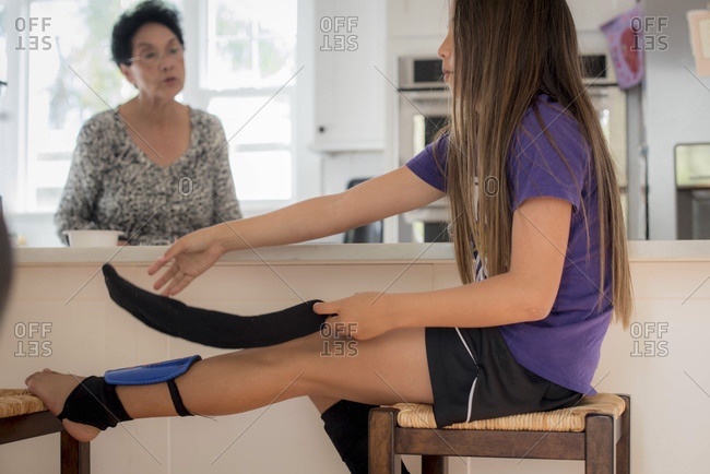 Girl removing shin guards in kitchen