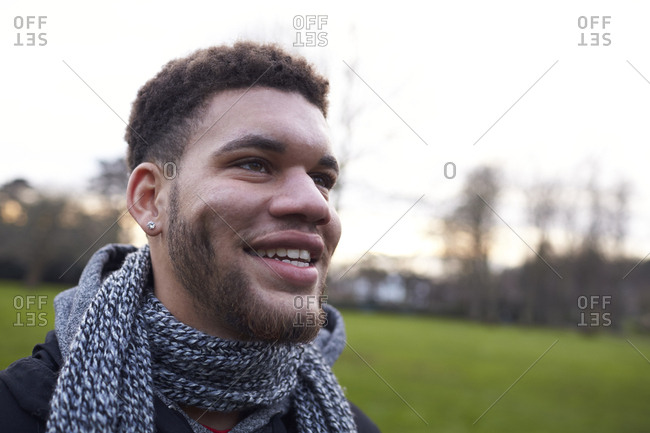 Head And Shoulders Portrait Of Young Man Walking In Park
