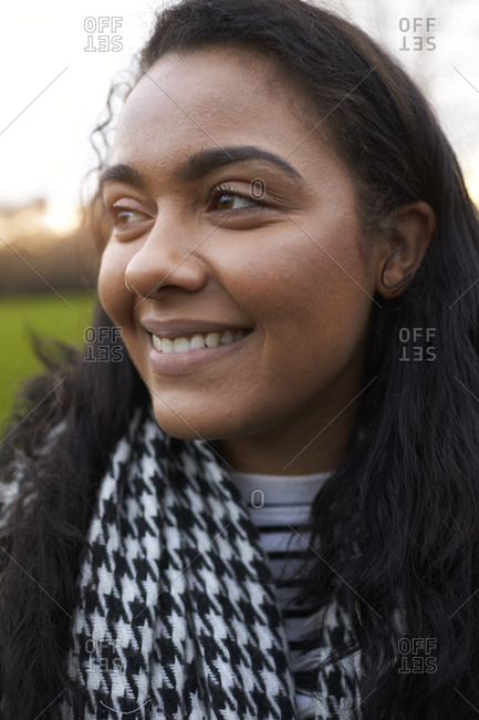 Head And Shoulders Portrait Of Young Woman Walking In Park