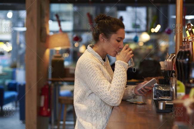 Young Woman Sitting In Bar Sending Text Message
