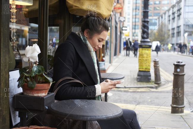 Young Woman Sitting Outside Coffee Shop Reading Text Message