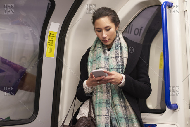 Woman Standing In Metro Carriage Looking At Text Message