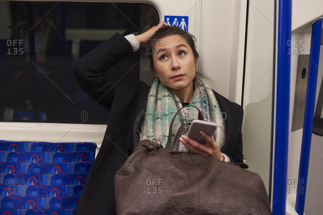 Woman Sitting In Metro Carriage Looking At Text Message