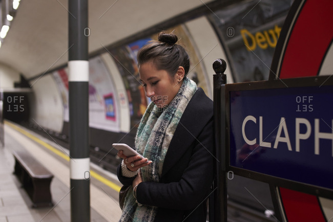 Woman Standing On Metro Platform Looking At Text Message