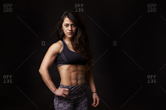 Waist up portrait of muscular dark haired young woman
