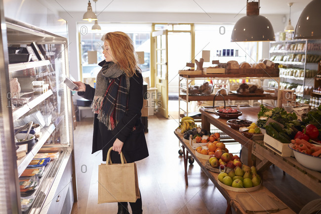 Woman Looking In Refrigerated Display Of Delicatessen