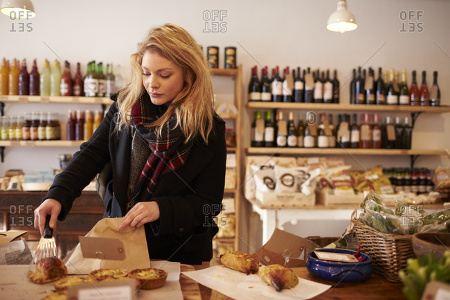 Woman Buying Baked Quiche In Delicatessen