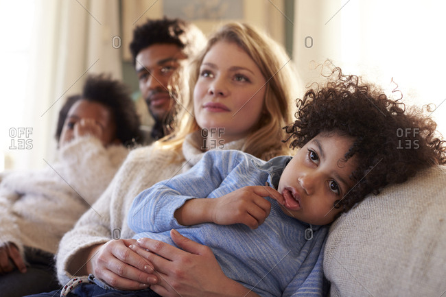 Family Relaxing On Sofa At Home Watching Television Together