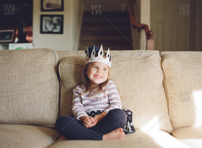 Girl in toy crown on couch