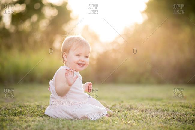 Toddler waving on summer lawn