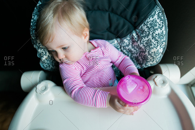 Girl in high chair with sippy cup