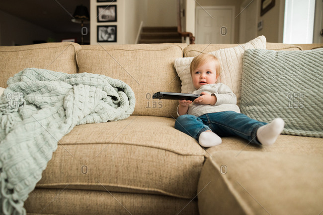 Toddler on couch with a remote