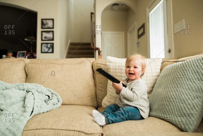 Laughing toddler with a remote