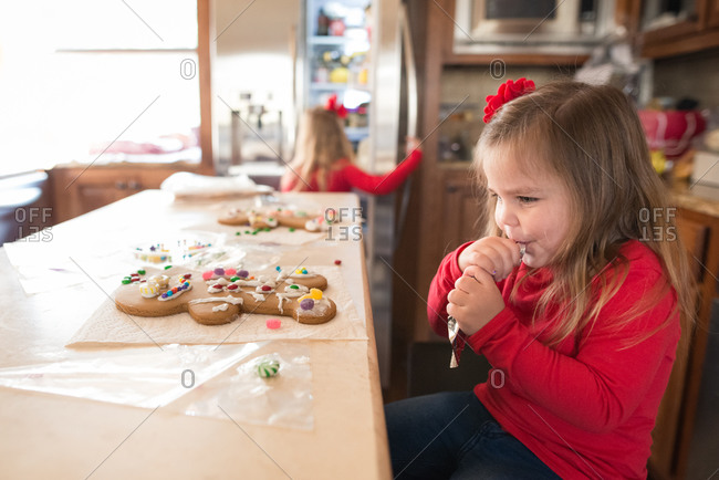 Girl eating frosting for Christmas cookies
