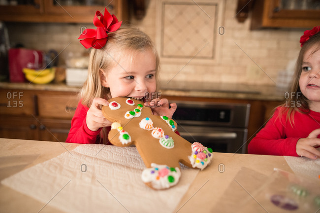 Girl biting gingerbread man cookie