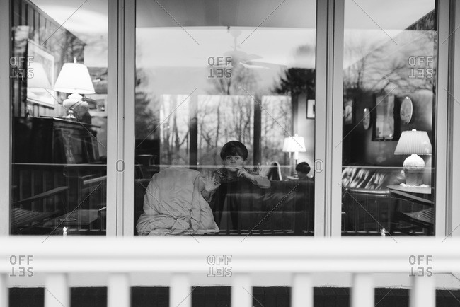 Boy looking out picture windows with reflections of the winter landscape