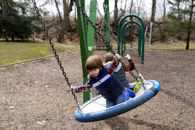 Two boys playing giant disk swing
