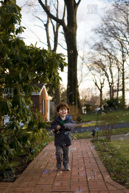 Boy chasing colorful bubbles in the evening light