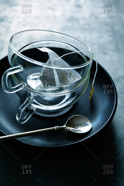 Two empty glass teacups and a teabag of green tea