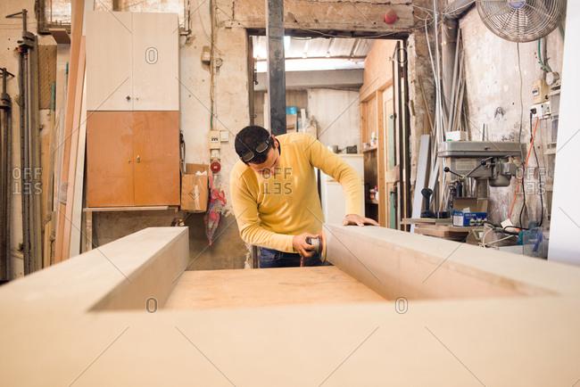 Man sanding down furniture