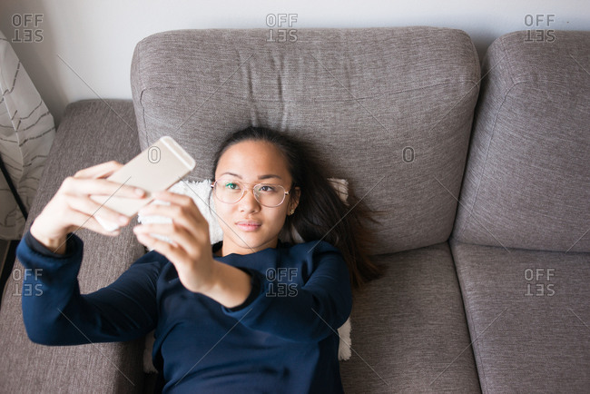 Woman on couch taking selfie