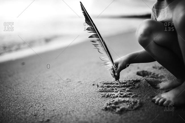 Boy writing in sand with feather