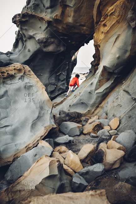 Boy climbing rocks on beach