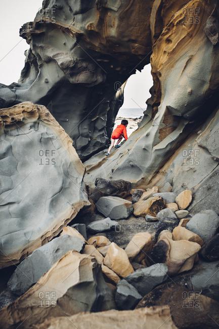 Boy climbing rocks on beach