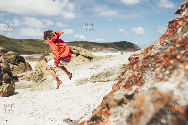 Boy leaping from beach rocks