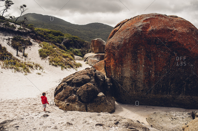 Boy gazing at beach boulder