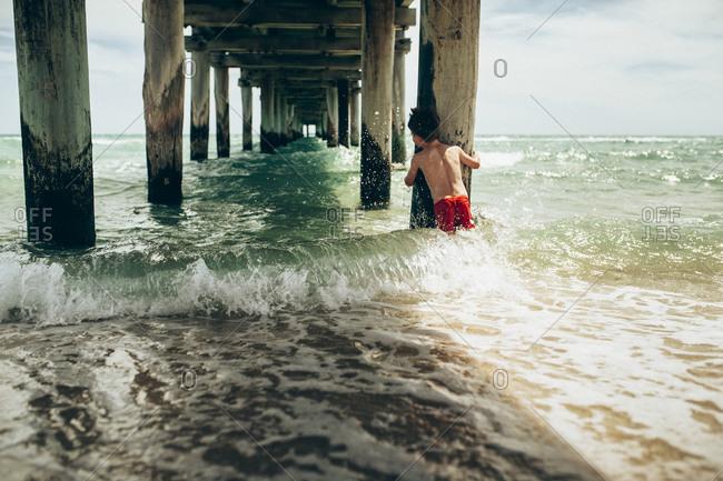 Boy holding pier pillar