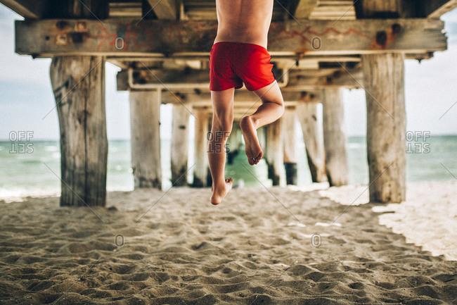 Boy midair under beach pier