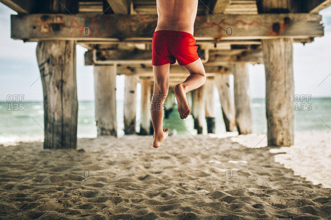 Boy midair under beach pier