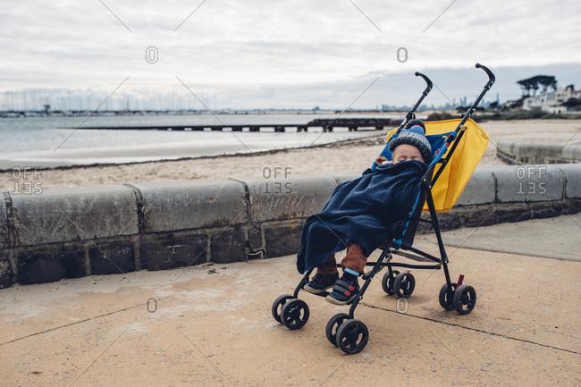 Boy asleep in stroller on beach