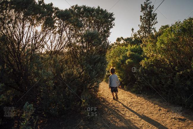 Boy on coastal trail with long shadows