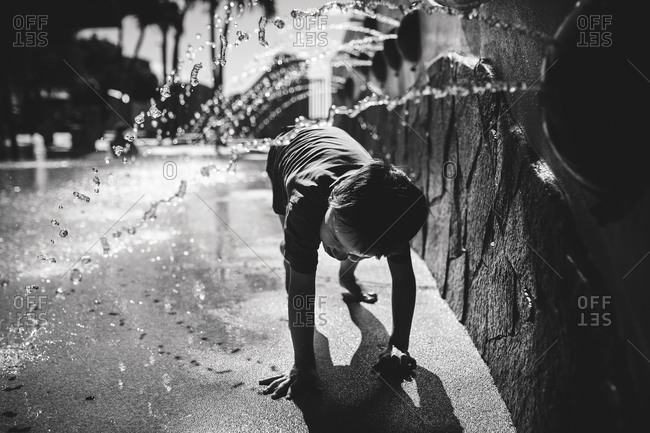 Boy playing in park fountain