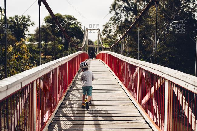 Boy on scooter crossing bridge