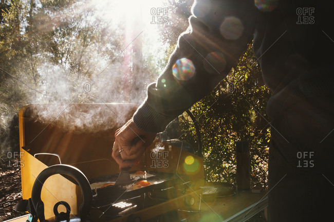 Man cooking eggs on a grill