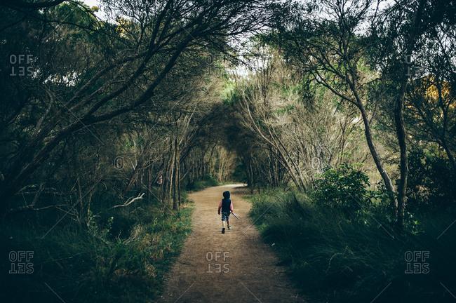 Boy walking down forest path