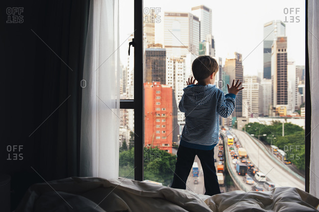Boy at window with city view