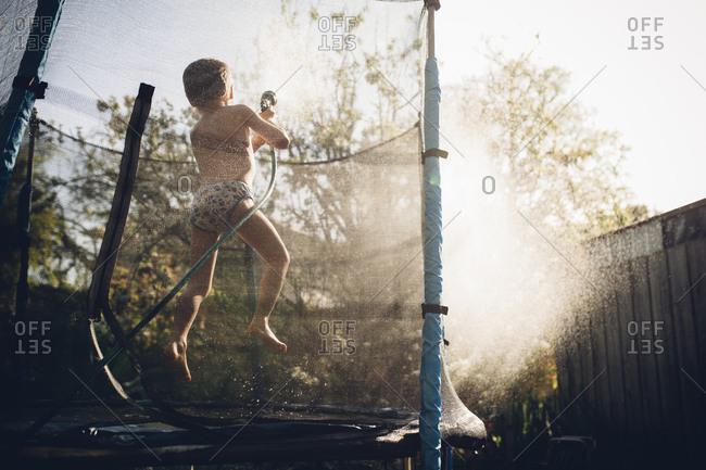 Boy on trampoline spraying hose