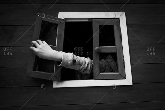 Kid's hand touching playhouse window
